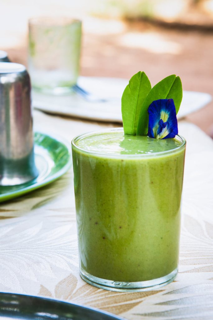 A green and minty smoothie with a purple flower garnish