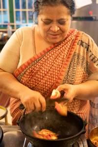 Abida Rasheed cuts tomato into a wok.