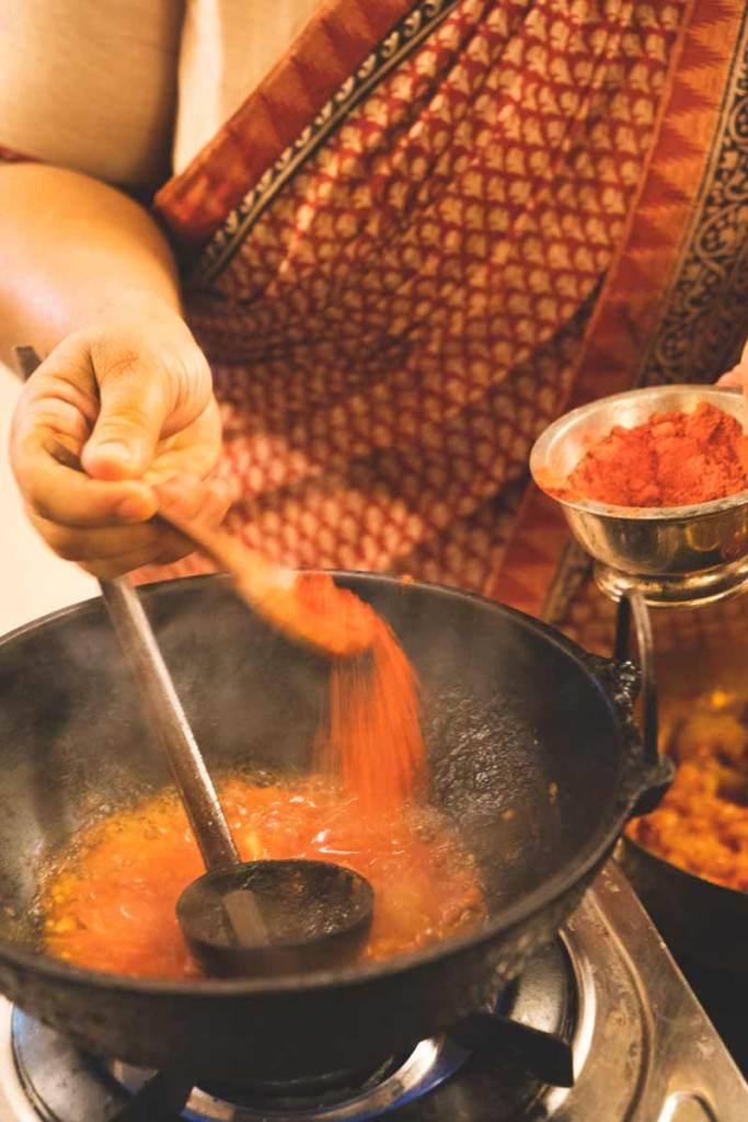 Abida Rasheed sprinkles chili powder into a wok
