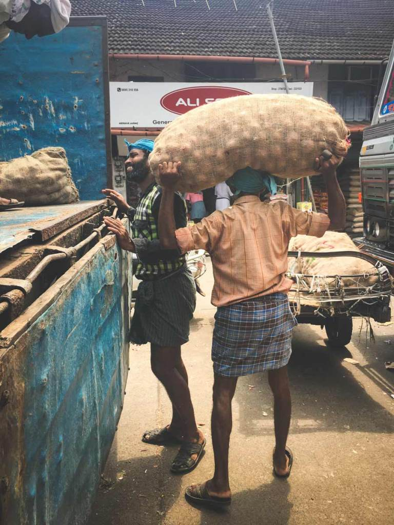 Big-Bazar-man packing-onions on his head.