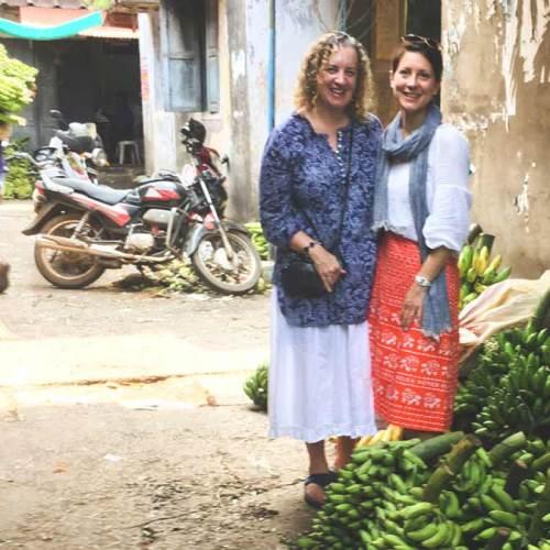 Pauli-Ann and Karen standing near bananas in Kozhikode (Calicut)