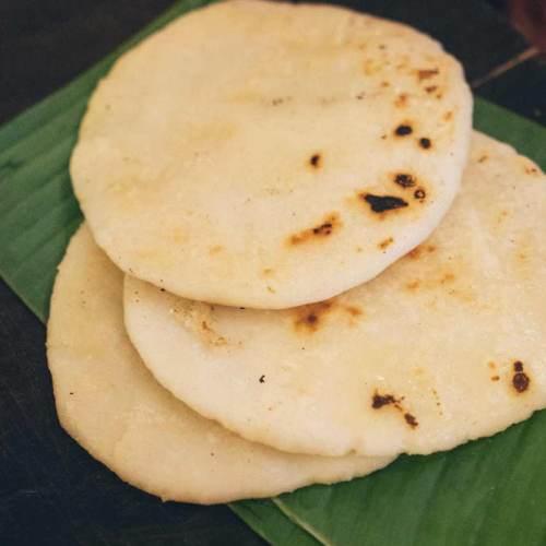 Three grilled pathiri bread sitting on a green banana leaf
