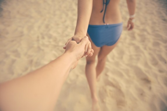 young-couple-holding-hands-and-walking-on-beach