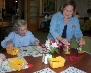 Lion Marcia Selva presents gifts to bingo players at Fairfax Nursing Centger
