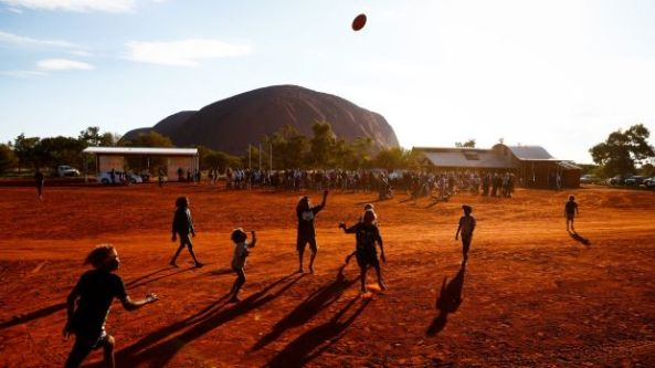 Children play footy during the closing ceremony in the Mutitjulu community of the First Nations National Convention.
