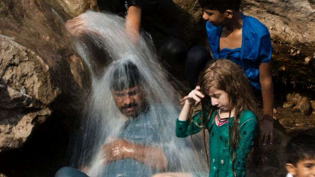 A family cools off in a stream during a heat wave last month in Islamabad, Pakistan.