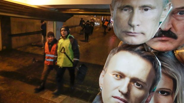 Face masks depicting Russian President Vladimir Putin, top, and Russian opposition leader Alexei Navalny, among others ...