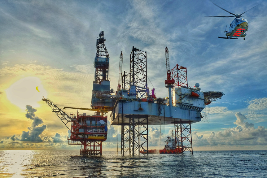An oil platform at sea with a helicopter flying away from it