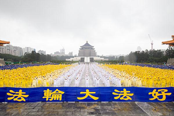 約6400名來自台灣及世界各地部分法輪功學員,11月25日齊聚在中正紀念堂排字,雖然台北雨勢不斷,但他們風雨無阻。圖為法輪功學員演煉功法。(白川/大紀元)