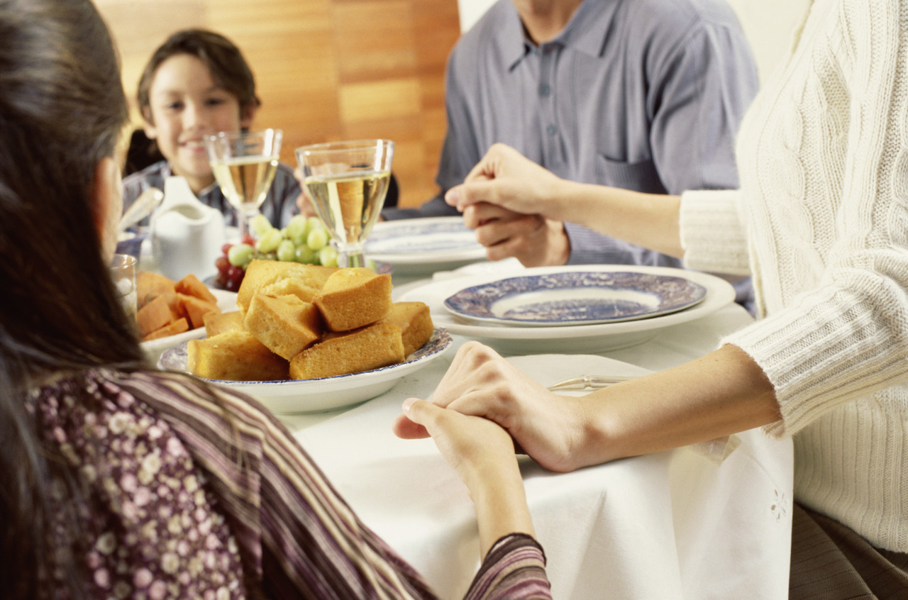 Portrait Of A Family Saying Grace Before Eating Dinner
