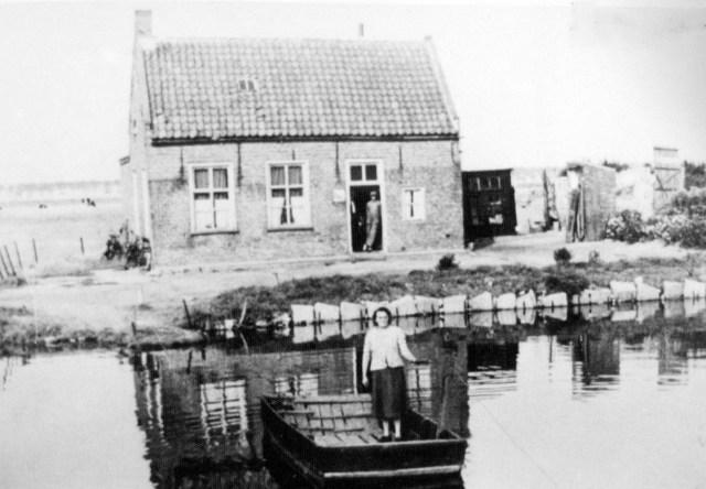 Tonia van 't Veer (mevrouw de Jong- Jongeneelen) op het pontje voor het Veerhuis, jaren 1950. Tot 1960 werd je voor 5 cent naar de overkant gebracht. In 1960 stopte Tonia en daarmee het voetpontje. Foto: Juffrouw Heijnen