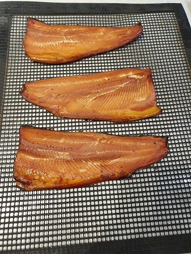 Smoked trout sitting on mesh mat