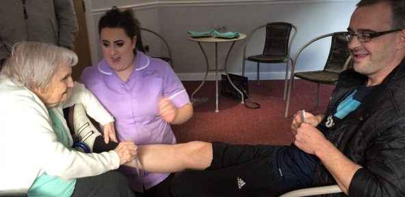Ninety-three-year-old waxes care worker's legs to fundraise for dementia dolls