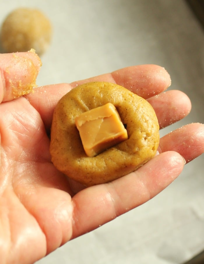 Unbaked pumpkin snickerdoodle dough ball with a caramel sunk into it.