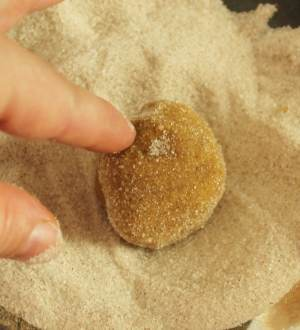Dough ball being rolled in cinnamon sugar mixture in a bowl.