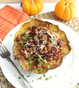 overhead view of Stuffed Acorn Squash on a white plate with a fork on it.