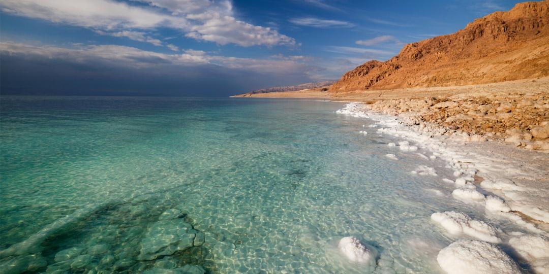 Dead Sea blue water against read rock with salt