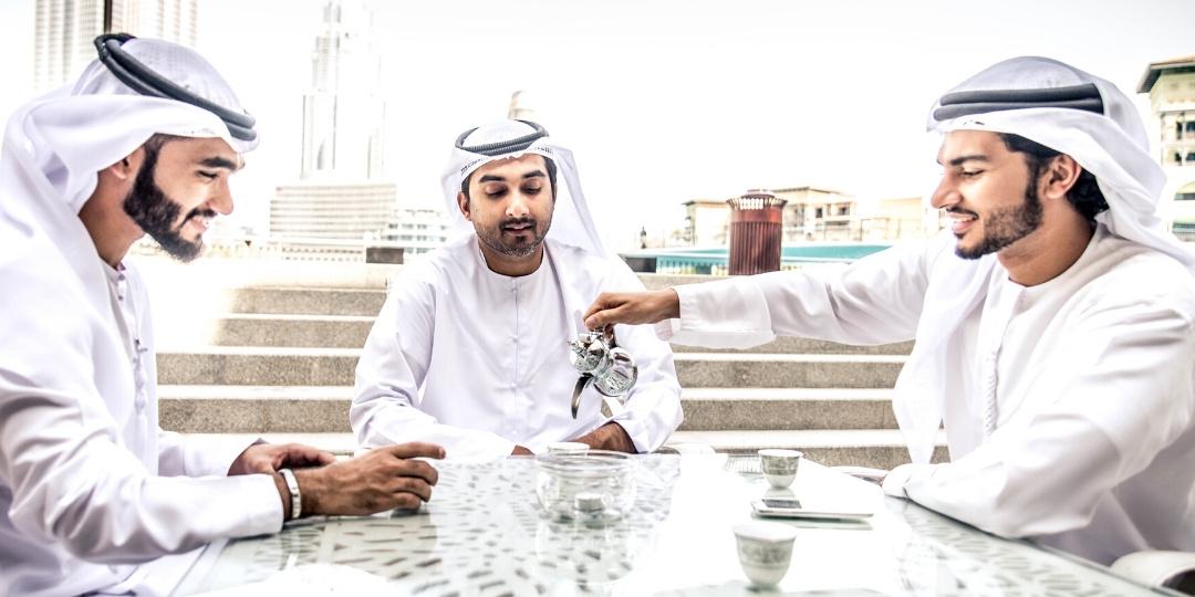 Arab Men in dishdashas drinking coffee