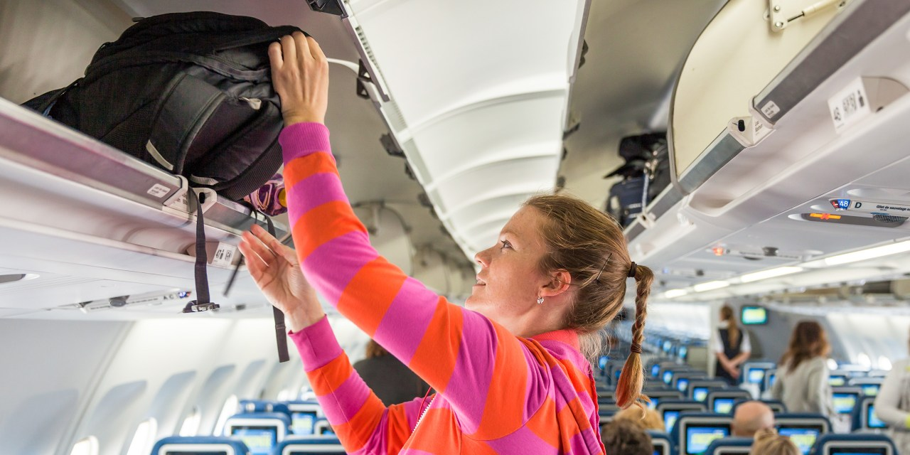 woman putting hand luggage on overhead plane; Courtesy of Eduard Goricev/Shutterstock