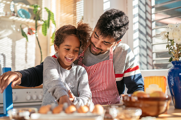 Smiling african american father and daughter baking in the kitchen;Courtesy of bbernard/Shutterstock
