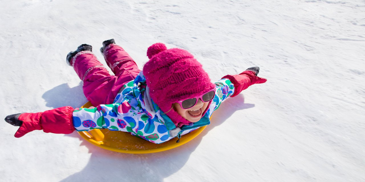 Girl Sledding in winter; Courtesy of YanLev/Shutterstock.com