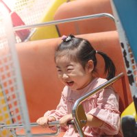 Young Asian Girl on Amusement Park Ride; Courtesy of Hans P./Shutterstock.com