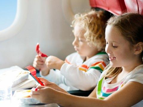Kids Eating Snacks On A Plane; Courtesy of FamVeld/Shutterstock.com