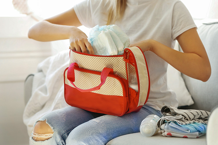 Woman packing her bag with diapers and wipes; Courtesy of Africa Studio/Shutterstock