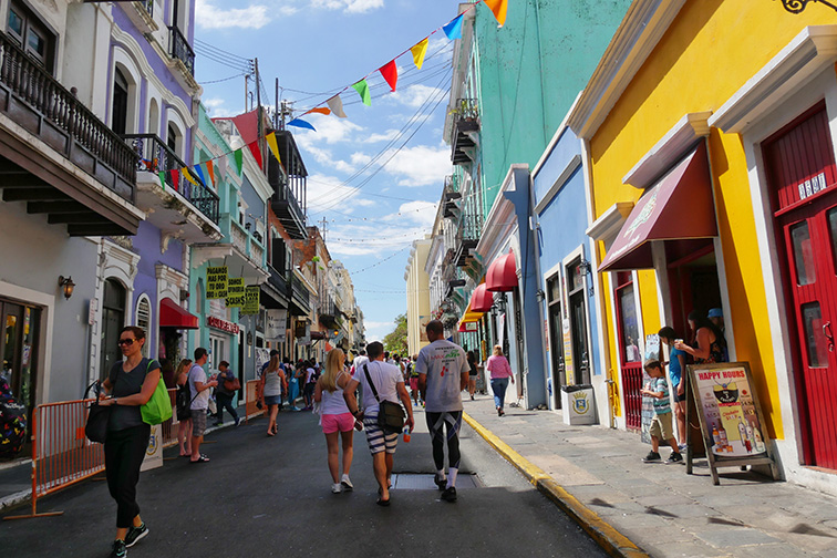People walking along one of the busy streets of Old San Juan, Puerto Rico; Courtesy of RaksyBH/Shutterstock