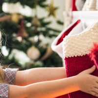 girl holding christmas stocking; Courtesy of Rawpixel/Shutterstock