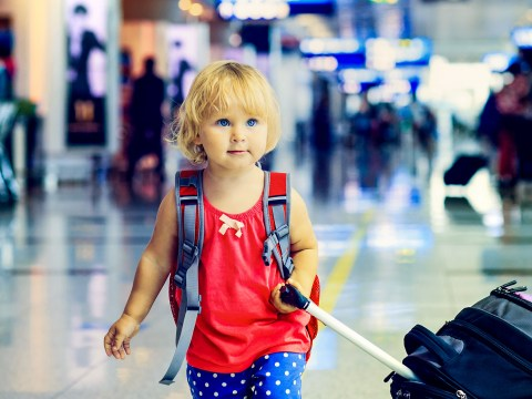 ittle girl with suitcase travel in the airport; Courtesy of NadyaEugene/Shutterstock