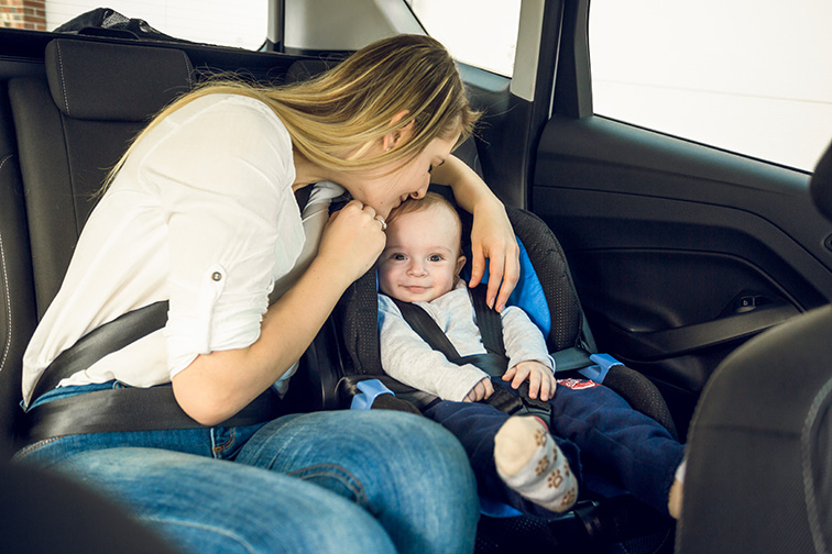 Portrait of happy young mother sitting on back seat with her baby; Courtesy of kryzhov/Shutterstock