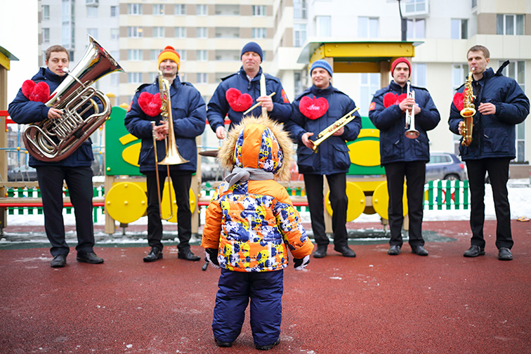 Brass band of six musicians play music and child looks at their on playground at winter day, ; Courtesy of Pavel L Photo and Video/Shutterstock