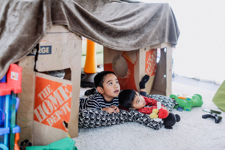 two kids building an indoor fort with pillows and boxes
