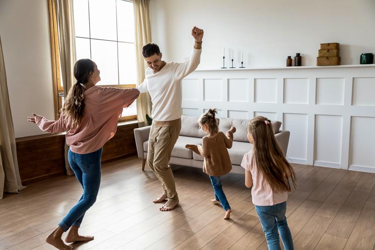 family dancing around living room; Courtesy fizkes/Shutterstock
