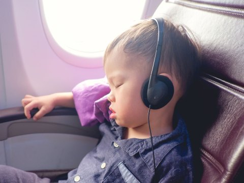 Asian Toddler Wearing Headphones on Plane; Courtesy of Yaoinlove/Shutterstock.com