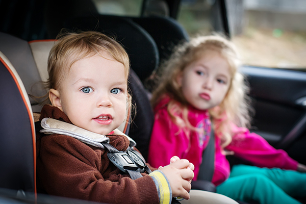 Little Boy and Girl in Backseat of Car