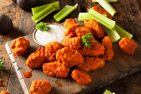 Original Buffalo wings paired with celery and glistening with sauce.