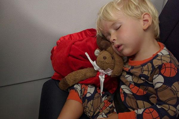A little boy sleeping on a plane.
