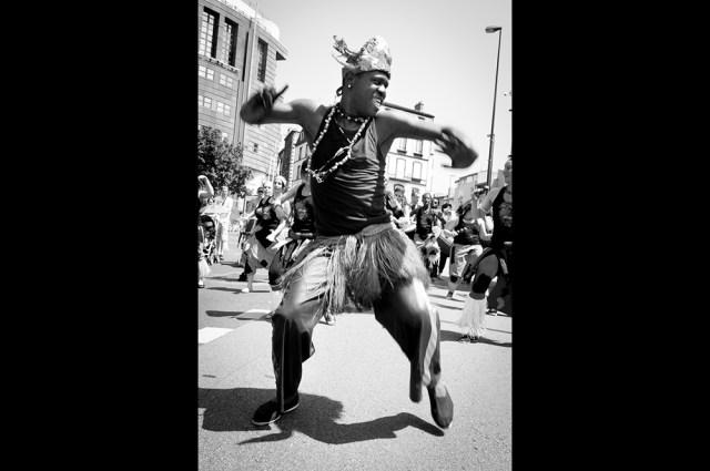 Photographie noir et blanc d'un homme noir pendant le carnaval de clermont-ferrand, appartenant à une troupe de danse africaine.
