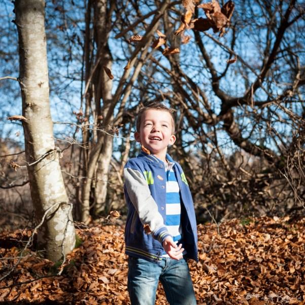 Portrait d'un petit garçon dans la forêt en train de jouer avec des feuilles d'automne. Image extraite d'un shooting en extérieur dans les volcans d'auvergne par fanny reynaud photographe professionnelle à clermont-ferrand.