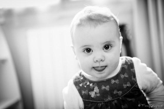 Photographie d'une petite fille de deux ans en noir et blanc qui nous offre un beau regard. © Fanny Reynaud photographe à domicile dans le puy-de-dome pour séance photo de famille chez vous.