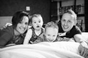 Photo de famille originale et décalée dans le lit familial : les parents et leurs deux enfants sourient. Extrait d'une séance de portrait à domicile par une photographe professionnelle de clermont-ferrand.