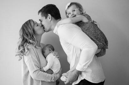 Séance photo à domicile à clermont-ferrand de jeunes parents avec un bébé et une petite fille. Photographie noir et blanc par un photographe professionnel d'auvergne.