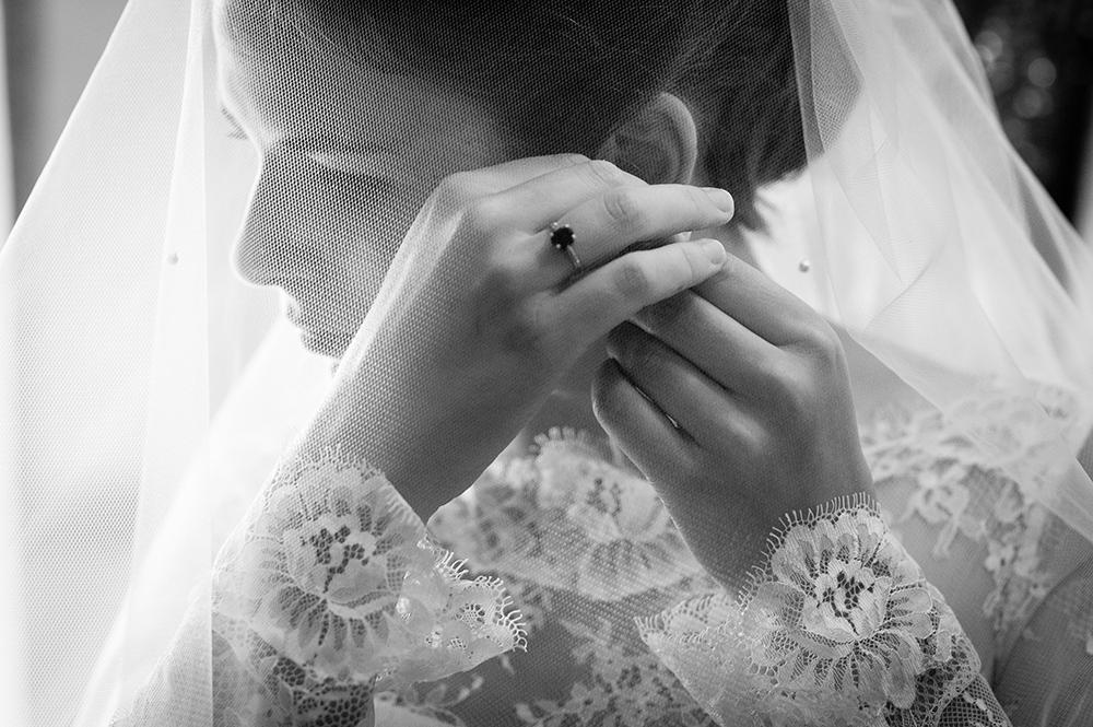 Habillage de la mariée venant de passer son voile, photographie noir et blanc prise par un photographe professionnel de clermont-fd.