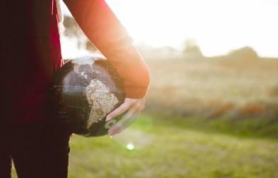 Women holding globe in hands girl earth outdoors green grass