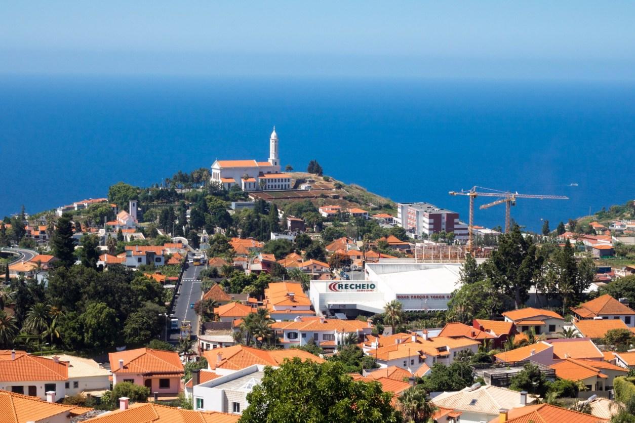 вид из пико-дос-барселуш с точки зрения вида через здания с оранжевой крышей и церковь в городе с океаном на заднем плане-мадейра-маршрут-7 дней