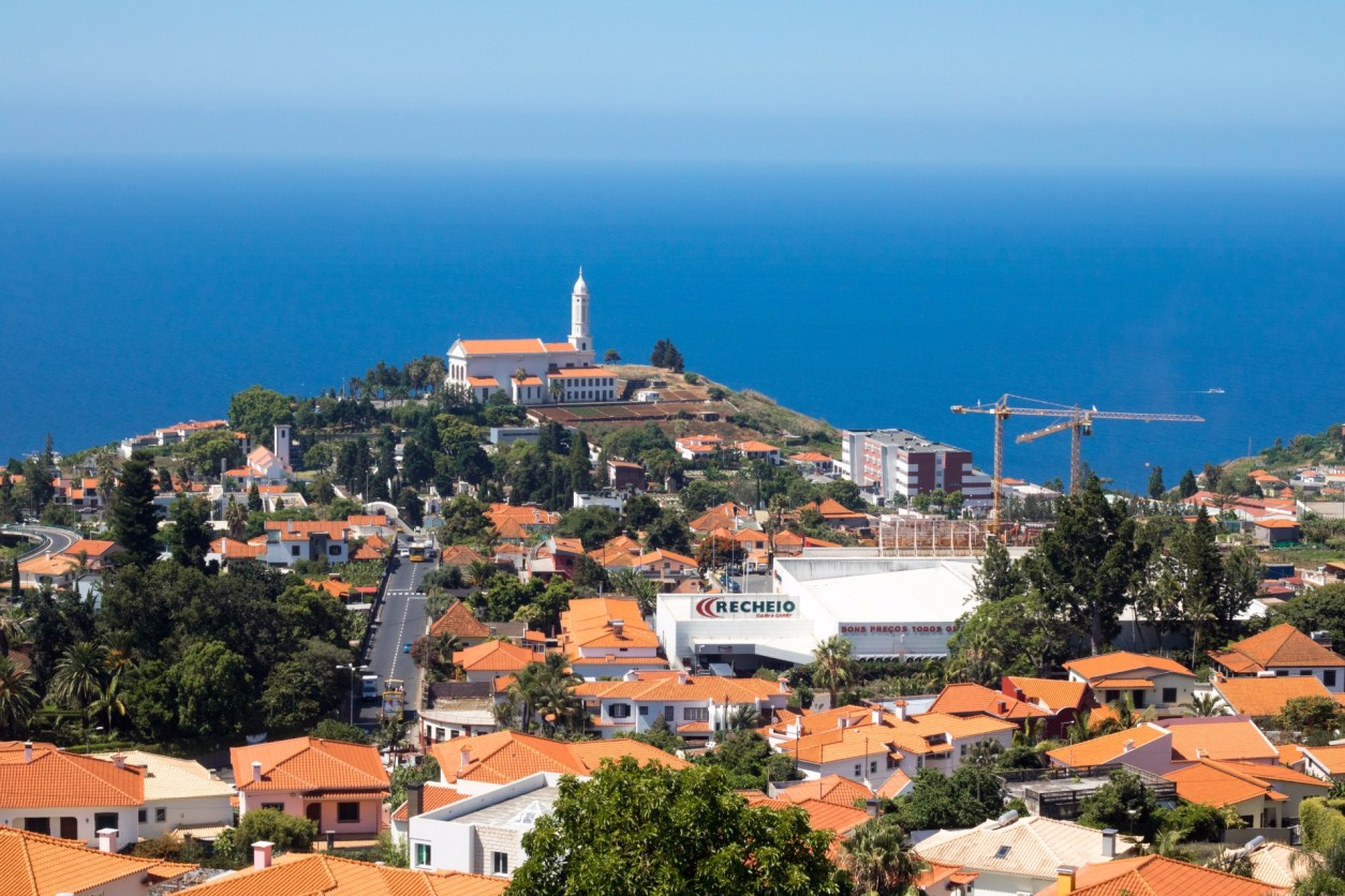 view-from-pico-dos-barcelos-viewpoint-looking-out-across-orange-roofed-buildings-and-church-in-city-with-ocean-in-background-madeira-itinerary-7-days