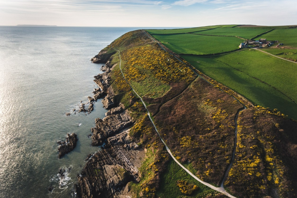 Rugged coastline, cliffs, green fields. Rocks on the shore. Blue sea and blue skies. Sunset over a cliff. Croyde Devon. 17 Beautiful Places to Visit in Devon for a Great Day Out. Devon England. Devon UK. Things to do in Devon. Places to see in Devon. What to see in Devon. Things to see in Devon. What to do in Devon. Devon attractions. Devon top attractions. Devon travel blog. Devon travel guide. The English Riviera. Exeter. Plymouth. Dartmouth. Dartmoor National Park. Exmoor National Park. Salcombe. Clovelly. Totnes. Appledore. Watermouth. Croyde. Woolacombe. Dartmouth. Ilfracombe. Beer. Burgh Island. Lundy Island. Click through to read more...
