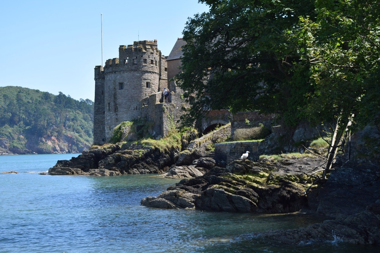 Dartmouth Castle. Old, historic castle on a lake. Blue waters and blue skies. Tree and rocks. 17 Beautiful Places to Visit in Devon for a Great Day Out. Devon England. Devon UK. Things to do in Devon. Places to see in Devon. What to see in Devon. Things to see in Devon. What to do in Devon. Devon attractions. Devon top attractions. Devon travel blog. Devon travel guide. The English Riviera. Exeter. Plymouth. Dartmouth. Dartmoor National Park. Exmoor National Park. Salcombe. Clovelly. Totnes. Appledore. Watermouth. Croyde. Woolacombe. Dartmouth. Ilfracombe. Beer. Burgh Island. Lundy Island. Click through to read more...